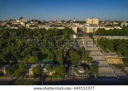 Elevated drone image of the Potemkin Stairs and Prymorski Boulevard with Istanbul Pakr and the Odessa Skyline behind. Taken at sunrise on a summer morning.