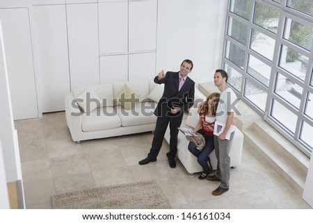 Elevated full length view of a male real estate agent showing couple new home - stock photo