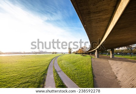 Elevated highway bridge over beautiful green field - stock photo