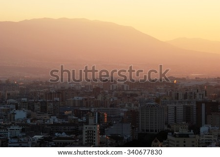 Elevated view across the city rooftops towards the mountains at dusk, Malaga, Costa del Sol, Malaga Province, Andalusia, Spain, Western Europe. - stock photo