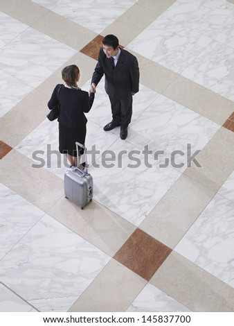 Elevated view of a businessman and businesswoman shaking hands on tiled floor - stock photo