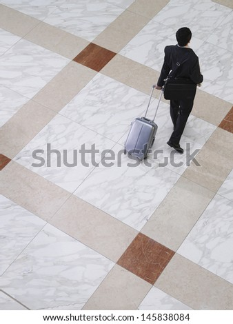 Elevated view of a businessman walking with suitcase on tiled floor - stock photo