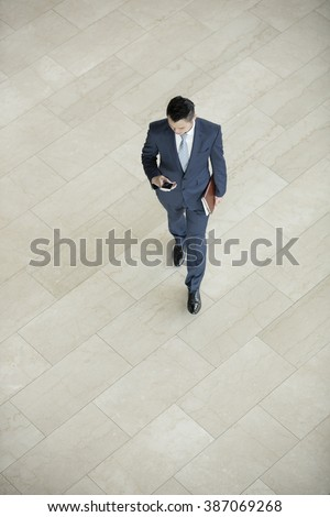 Elevated view of a Chinese businessman using his Smart phone in modern city.
