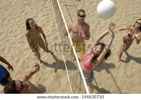 Elevated view of a group of young people playing volleyball on beach - stock photo