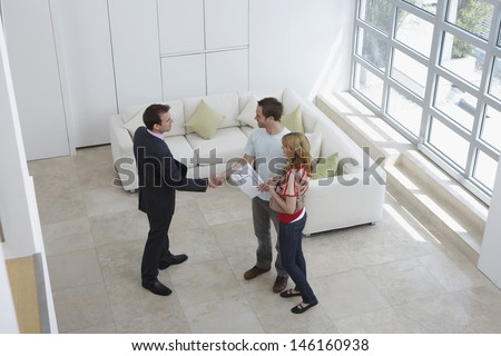 Elevated view of a male real estate agent shaking hands with a man by woman in new home - stock photo