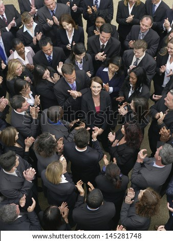 Elevated view of business group looking at female woman standing in middle - stock photo