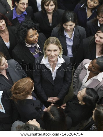 Elevated view of business group looking at female woman standing in middle