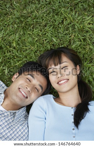 Elevated view of happy couple lying on grass - stock photo