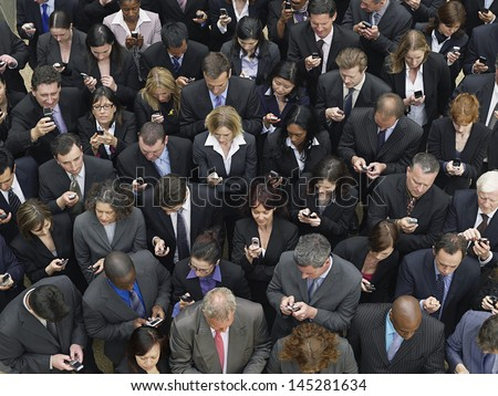Elevated view of large group of business people text messaging with mobile phones  - stock photo