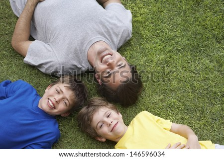 Elevated view of smiling father and two sons lying on grass - stock photo
