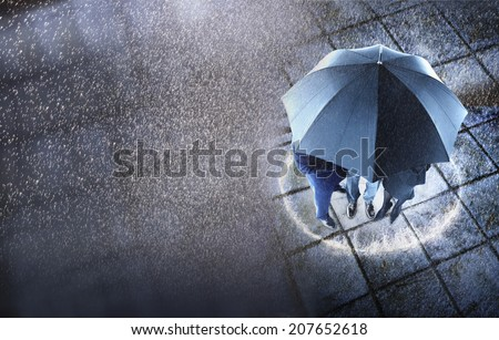 Elevated view of three businesspeople sheltering under one umbrella - stock photo