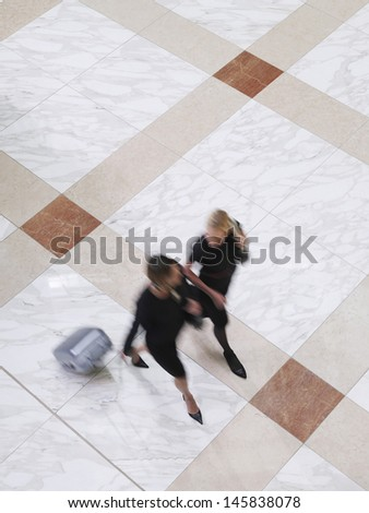 Elevated view of two blurred businesswoman walking with suitcase on tiled floor - stock photo