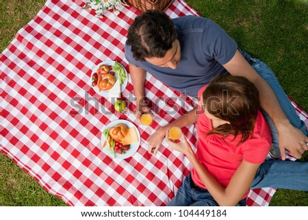 Elevated view of two friends looking into each others eyes while they hold glasses as they lie on a blanket with a picnic - stock photo