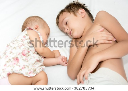 Elevated view of two little sisters sleeping in bed at home - stock photo