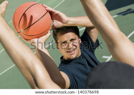 Elevated view of two men playing basketball on a sunny day - stock photo