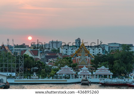Elevated view of Wat Arun, Temple of Dawn,  complex and wharf with sunset sky on the background. Urban Bangkok scene with Buddhist temple - stock photo