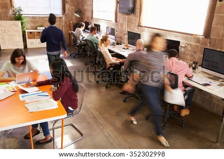 Elevated View Of Workers In Busy Modern Design Office - stock photo