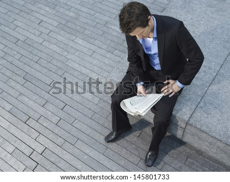 Elevated view of young businessman reading newspaper while sitting on wall