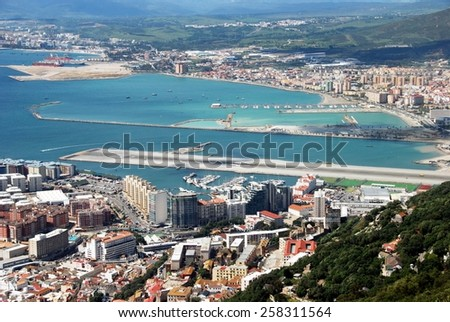 Elevated view over town and airport runway from cable car station with the Spanish coastline to the rear, Gibraltar, United Kingdom, Western Europe. - stock photo