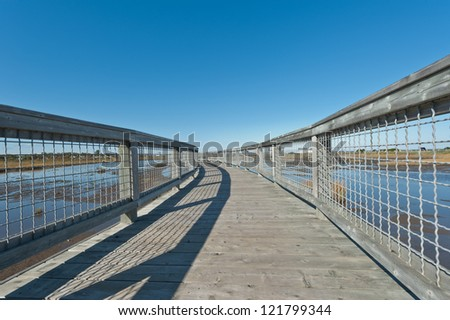 Elevated walkway above a salt marsh during a sunny day