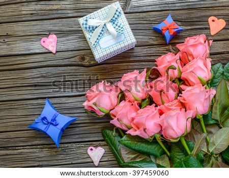 Eleven pretty stemmed pink roses and little three little Valentines gift boxes next to heart shapes over old wood background with copy space - stock photo