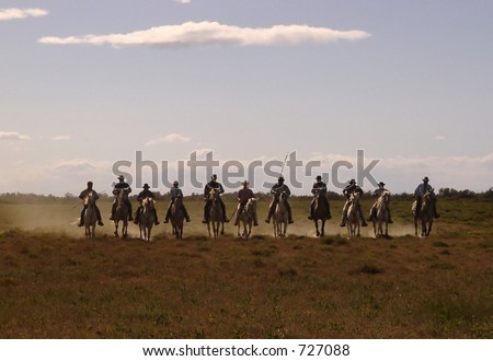 eleven silhouetted cowboys in straight line riding in dusty field - stock photo