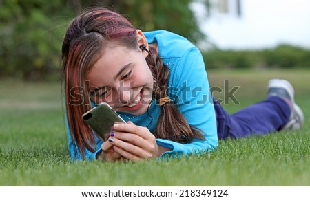 Eleven year old child happily listening to music with handheld electronic device. - stock photo