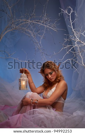 Elf in magical winter forest with lantern. - stock photo