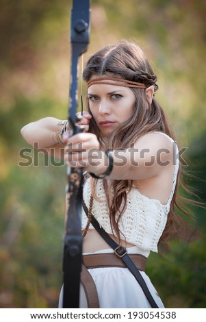 elf mythical hunter  girl shooting bow and arrow - stock photo
