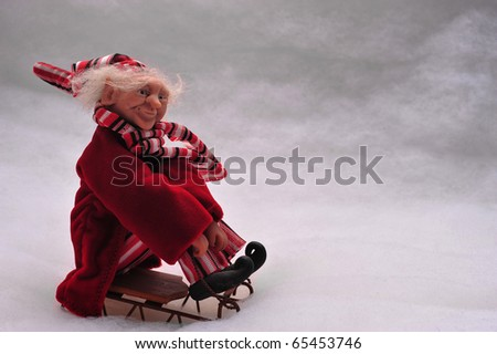 elf riding a sled in the snow. - stock photo