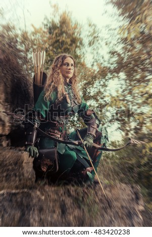 Elf woman in green leather armor with the bow and arrows on the rocks background.