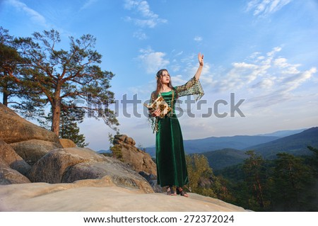 Elf woman in the mountains against the sky waving hands - stock photo