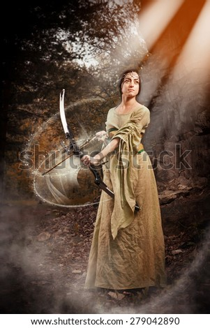 Elf woman with the magic bow on the autumn forest background. - stock photo
