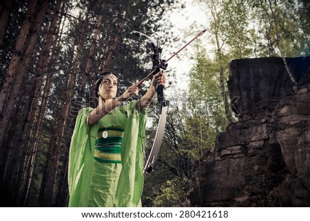 Elf woman with the magic bow on the forest background. - stock photo