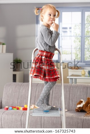 Elfish little girl standing on top of ladder, thinking impishly.