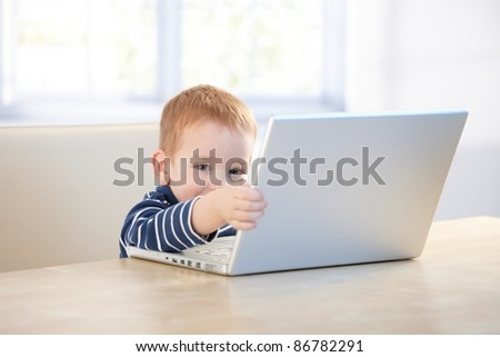 Elfish little kid playing with laptop at home, sitting at desk.? - stock photo