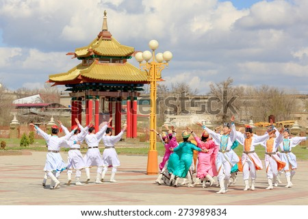 ELISTA, REPUBLIC OF KALMYKIA, RUSSIA - APRIL 20, 2015: Dance group of Kalmyk national costumes dance on the background of a Buddhist temple in Elista, Kalmykia, Russian Federation  on April 20, 2015 - stock photo
