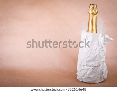 Elite bottle of expensive champagne. Decorated with tulle. Soft beige background. Place for your text, wishes, logo. Nice New Year, Christmas, Wedding or other holiday mock up. Vignetted.