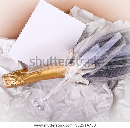 Elite bottle of expensive champagne. Decorated with tulle. Soft beige background. Place for your text, wishes, logo. Nice New Year, Christmas, Wedding or other holiday mock up. Vignetted. - stock photo