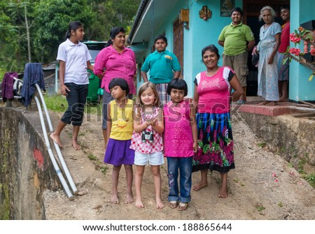 ELLA, SRI LANKA - MARCH 2, 2014: Little blonde girl posing with locals. Ella is famous for the tea plantations and stunning views across the countryside.