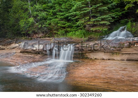 Elliot Falls, a waterfall in Upper Peninsula Michigan's Pictured Rocks National Lakeshore, cascades into Lake Superior at one end of Miners Beach. - stock photo