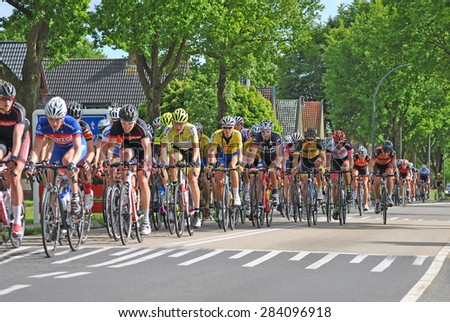 ELSPEET, THE NETHERLANDS, 3 JUNE 2015 - Cyclists racing through Elspeet during a national cycling race. - stock photo