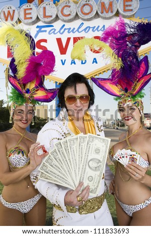 Elvis impersonator with happy casino dancers in front of a sign