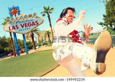 Elvis look-alike impersonator man in front of Welcome to Fabulous Las Vegas sign on the strip. People having fun and Viva Las Vegas concept image with Elvis impersonator doing some crazy moves. - stock photo
