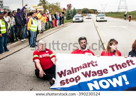 ELWOOD, ILLINOIS - OCTOBER 1, 2012: Protesters, including clergy members, stage a sit-down protest to block the entrance of the Walmart distribution center at a rally for Warehouse Workers Justice. - stock photo