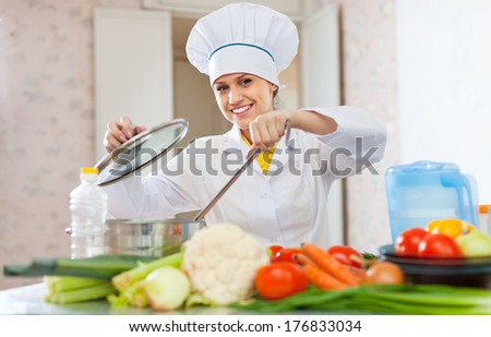 emale cook in uniform works with vegetables in kitchen - stock photo