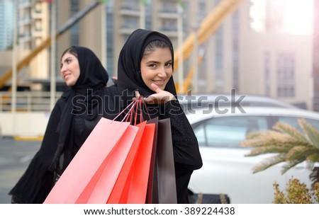 Emarati Arab women coming out of shopping in Dubai, United Arab Emirates. - stock photo