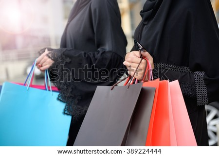 Emarati Arab women coming out of shopping in Dubai, United Arab Emirates. - stock photo