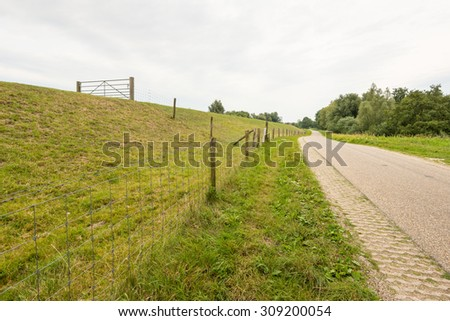 Embankment with a fence and a gate along a meandering country road in a Dutch landscape on a cloudy summer day. - stock photo