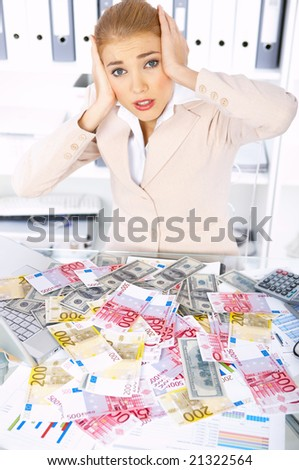 Embarrassed business woman with lots of cash on table - stock photo